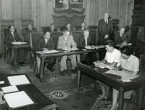 Gemeenteraad in de raadszaal. Voor v.l.n.r. de raadsleden: J. de Jong, H. Slaterus, P.J. Mani, W.C. Dijkstra, W.A. van den Brink (allen Partij van de Arbeid). Achter v.l.n.r.: R. Wijkstra, F. Heystra, J. Venema, E. Beeksma, B.B. Hartstra en J. Visser (niet zichtbaar) (allen Partij van de Arbeid). Stenografen: mej. Y. Weidema (links) en mej. W. Steffering. Bron: Beeldbank HCL. Fotograaf: Sj. Andringa.